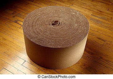 Roll of corrugated packing material shot on wood floor