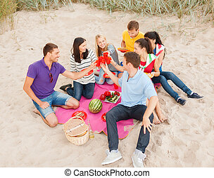 group of happy friends having picnic on beach - summer...