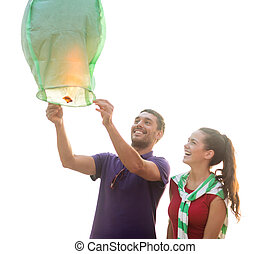 happy couple with chinese sky lantern on beach