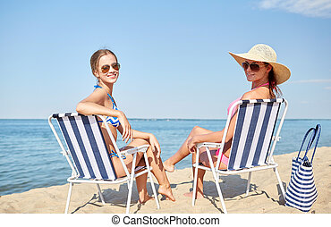 happy women sunbathing in lounges on beach - summer...
