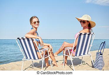 happy women sunbathing in lounges on beach - summer...