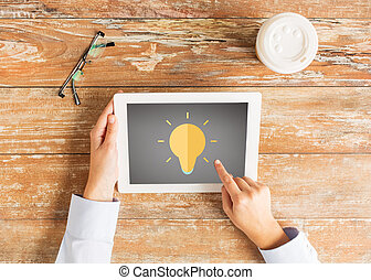 close up of hands with lighting bulb on tablet pc -...