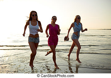 group of smiling women running on beach - summer vacation,...