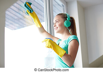 happy woman with headphones cleaning window - people,...