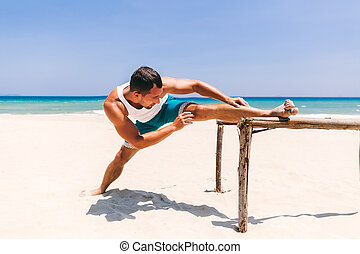 man stretching on the beach - man stretching and doing...