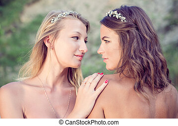 closeup portrait of 2 brunette and blonde young pretty women best friends with bare shoulders wearing silver diadems looking at each other on green summer outdoors background