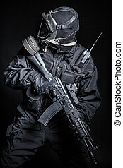 Russian special forces operator in black uniform and gas...