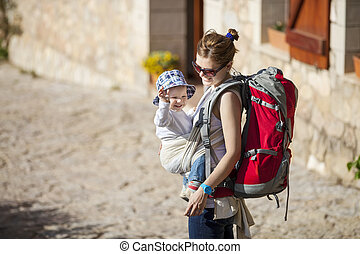 Woman tourist carrying her little son in sling - Young woman...
