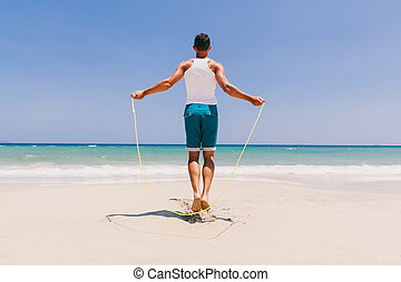 fitness man skipping on the beach - fitness man skipping on...