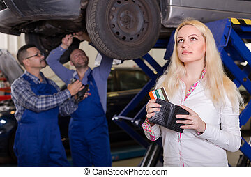 Girl in auto repair shop - Thoughtful blonde girl with...