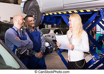 Woman and two auto mechanics - Smiling insurance agent...