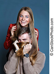Close up portrait of young couple over dark gray background
