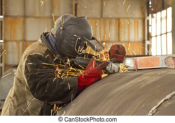 welder cleans the weld from slag grinding machine - welder...