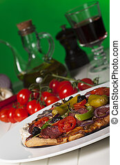Pizza on green background with ingredients