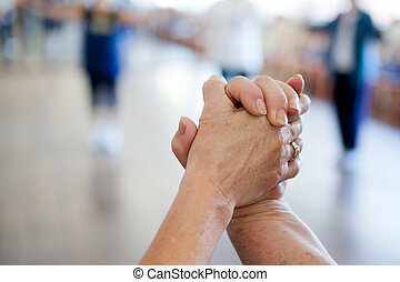Holding Hands - Image of two eldest women holding hands with...