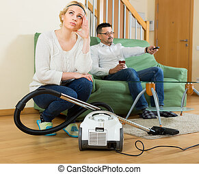 Upset woman cleaning around - Man resting on sofa with...