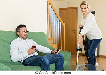 Wife hoovering room, husband relaxing - Happy wife hoovering...