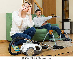 Upset woman with hoover looking at tired man on sofa...