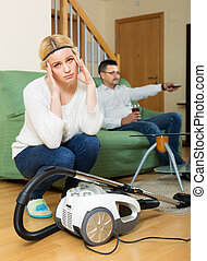 Sad woman with hoover looking at man on sofa watching TV