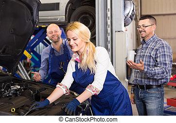 Female mechanic is fixing a car