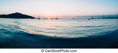 Sunrise on a small bay with anchored sailboats. -...