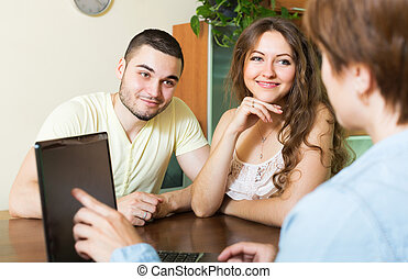 Couple signing agreement at home - Happy couple and real...