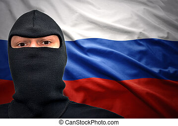 russian danger - dangerous man in a mask on a russian flag...
