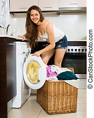 Nice woman with clothes near washing machine at home