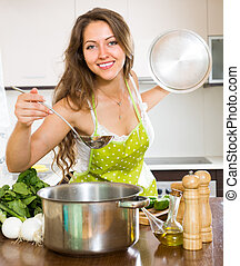 Woman cooking soup in kitchen - Smiling young housewife in...