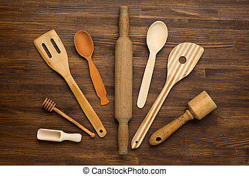 Wooden kitchen tools on vintage wooden background Top view