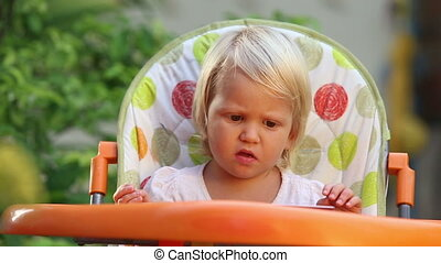 little girl sits in  chair and eats fruit