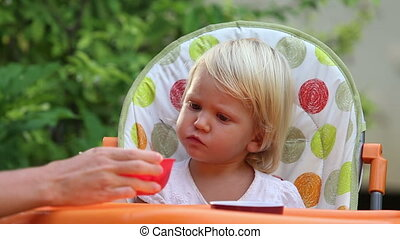 mother puts plate in front of little girl eating fruit