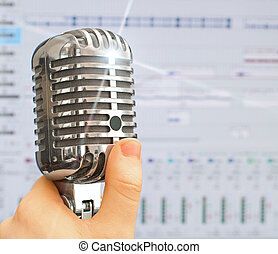 Hand holding retro microphone over recording software...