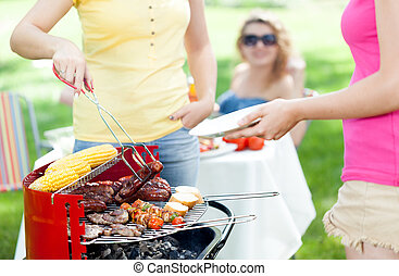 Host serving woman frazzled sausage on grill party