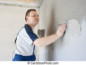middle-aged man worker putting plaster on the wall