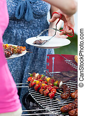 Woman serving dinner on barbecue party - Woman serving...