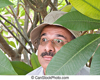 Private detective with sun hat hiding in the bushes
