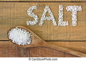 Salt in spoon on a wooden table - still life