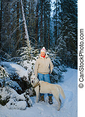 Woman with dog in winter forest on a walk