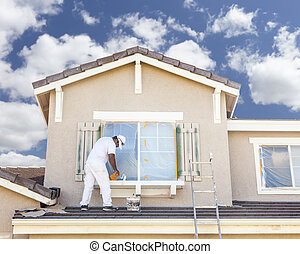 House Painter Painting the Trim And Shutters of Home - Busy...