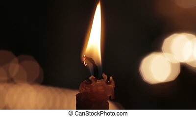 Single candle with flame fire dripping wax in church cathedral. Black macro