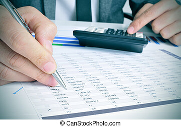 young businessman checking accounts - closeup of a young...