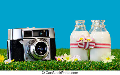 three bottles of milk with a camera in the grass