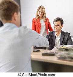 Business agreement - Two men shaking hands in an office and...