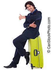 Corporate man sitting above the luggage showing thumbsup in...