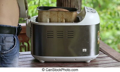 man takes container out of breadmaker and puts on table -...