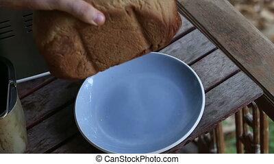 man hands put fresh bread on plate - european man hands put...