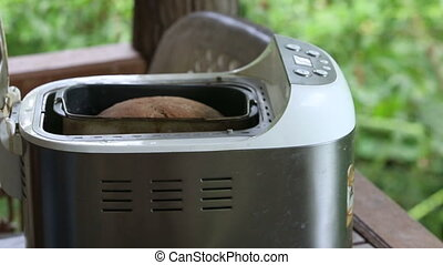 man hands open machine to take out bread - european man...