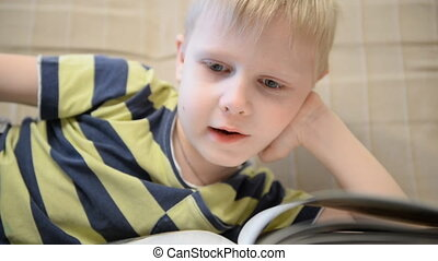 Boy 5 years reading a book at home on the couch