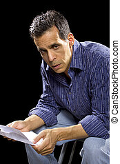 Unpaid Bills - stressed out man reading unpaid bills or...